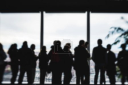 Photo for People silouette looking through windows of high view skyscraper - Royalty Free Image