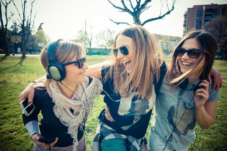 Photo for Three beautiful friends authentic in urban contest listening to music - Royalty Free Image