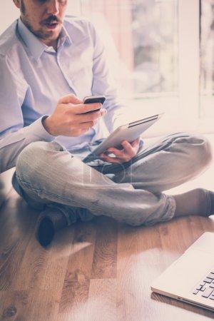 Photo pour Entreprise élégante multitâche multimédia homme utilisant des appareils à la maison - image libre de droit