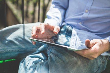 Photo pour Fermer les mains multitâche homme en utilisant tablette connexion wifi - image libre de droit