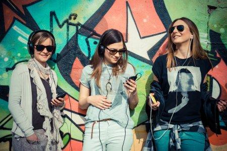 Three beautiful friends authentic in urban contest...