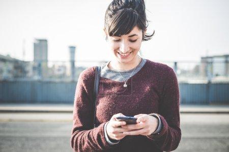 Photo pour Femme hipster belle jeune en utilisant le téléphone intelligent dans la ville - image libre de droit