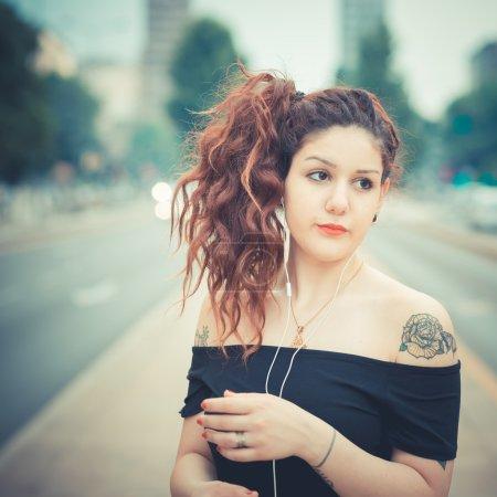 Photo pour Jeune belle femme hipster aux cheveux bouclés rouges écoutant de la musique dans la ville - image libre de droit