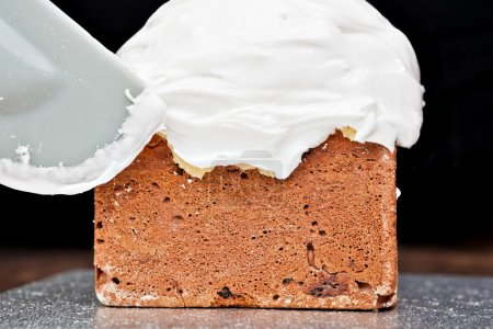 Creme auf Kuchen mit Spachtel verteilen