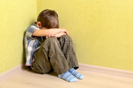 Little child boy wall corner punishment sitting...