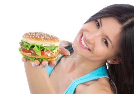 Photo pour Jeune femme avec une restauration rapide savoureux sandwich hamburger malsain à la main se préparer à manger isolé sur un fond blanc. Focus sur hamburger witn main . - image libre de droit