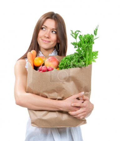 Photo for Happy young woman holding a paper shopping bag full of groceries, mango, salad, asparagus, radish, avocado, lemon, carrots on white background - Royalty Free Image