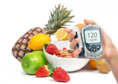 Photo pour Lecteur de glycémie de notion de diabète dans la main et aliments biologiques sains, citron, poire, pommes, fraîche bol de muesli céréales orange, ananas et petit déjeuner sur un fond blanc - image libre de droit