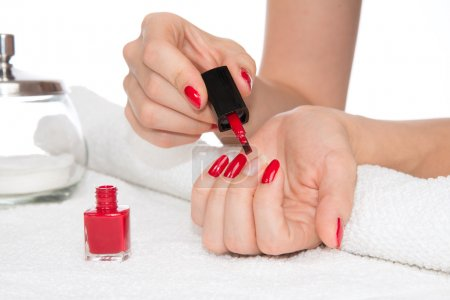 Woman hands doing manicure red nails