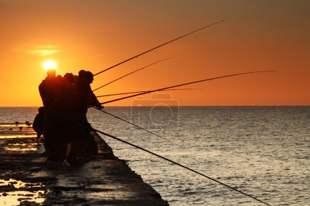 Fishermen on sunrise on the pier
