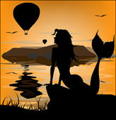 Mermaid silhouette on sunset background