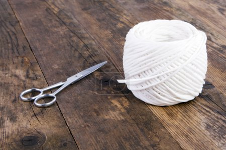 Scissors and twine ball, on a board.