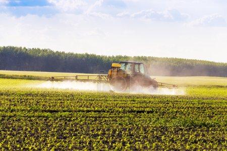 Farm tractor spraying a field.