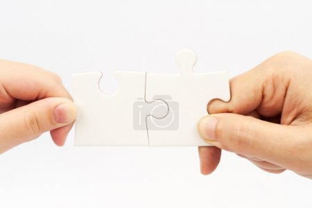 Photo for Two hands holding puzzle pieces and connecting them - Royalty Free Image