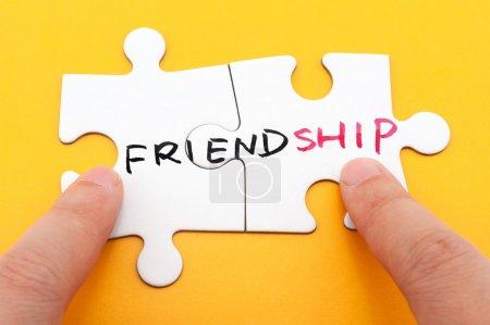 Foto de Palabra de amistad escrito en dos piezas de rompecabezas - Imagen libre de derechos