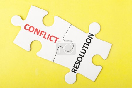 Photo for Conflict and resolution words printed on two pieces of puzzle - Royalty Free Image