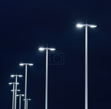 Modern street lights illuminated at night against ...