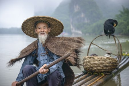 Photo for Cormorant fisherman and his bird on the Li River in Yangshuo, Guangxi, China. - Royalty Free Image
