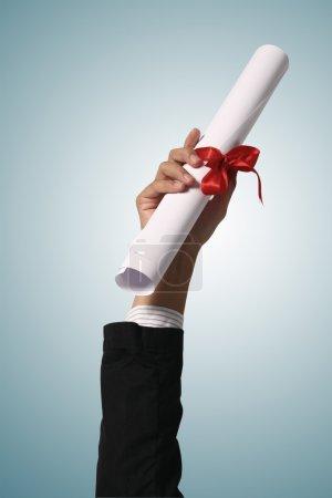 Photo pour Diplôme avec un ruban rouge à la main sur fond bleu - image libre de droit