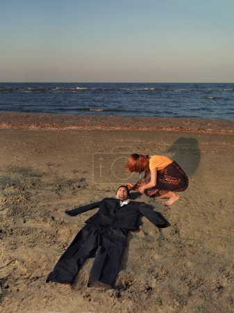 Photo for Exhausted young businessman stranded on sea shore, with an empty suit where his body should be, and a young woman comforting him - Royalty Free Image