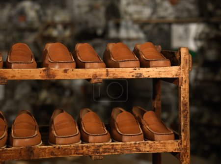 Photo for Detail of a storage zone in a shoe factory, with brown moccasins aligned on wooden shelves - Royalty Free Image
