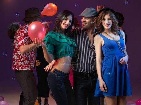 Photo pour Jeune homme tenant et danse avec deux filles qui sourire et posent pour la caméra, avec ballons, bulles et les gens danser en arrière-plan - image libre de droit