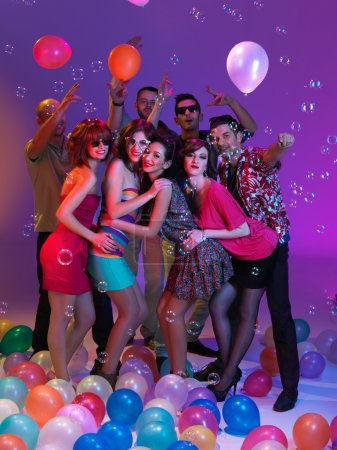 Photo for Young posing together, smiling and hugging each other, with lots of bubbles and colored balloons - Royalty Free Image