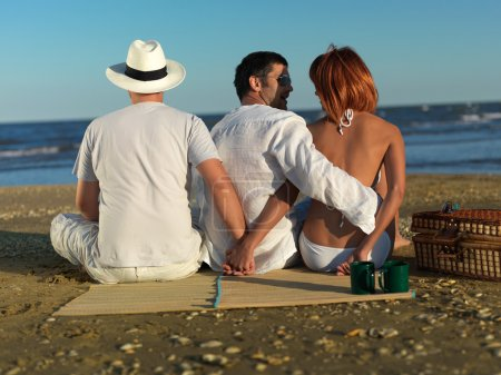 Photo for Young woman talking with the boyfriend, while holding hands with another man, at a picnic by the sea shore - Royalty Free Image