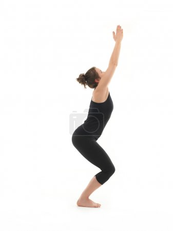 Photo for Demonstration of beginner yoga posture by young woman, dressed in blac, on white background, side view - Royalty Free Image