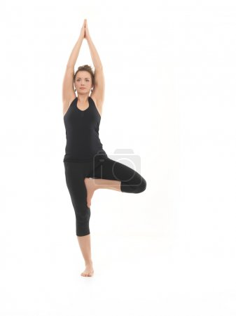 Photo for Frntal view of young woman sitting in yoga posture, dressed in blak, on white background - Royalty Free Image