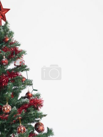 Photo for Detail of a christmas tree decorated with red garland, globes and star isolated on white background framed in the left border of the image - Royalty Free Image