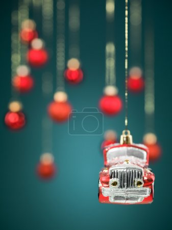 Photo for Closeup of hanging christmas small car decoration with golden strings on blue gradient background with blurred red globes - Royalty Free Image