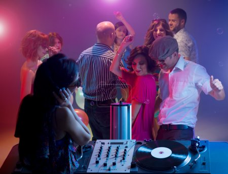 young couple dancing at party with female dj