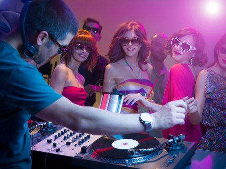 male dj playing music with turntables and headphones at a party with dacing in front of him wearing sunglasses, with other in background and colorful lights