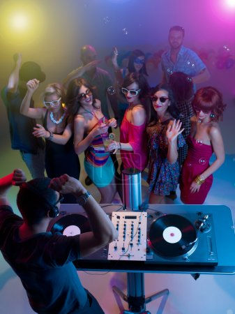 dj mixing music at party with dancing