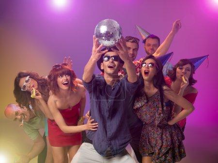 Photo pour Jeune homme caucasien beau tenant une boule de disco dans ses mains et le regardant étonné, avec d'autres heureux autour de lui avec des cornes de fête et des chapeaux, avec des lumières de colorfu en arrière-plan - image libre de droit