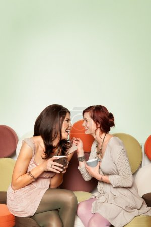 Photo for Two young beautiful caucasian girls sitting on colorful sofa with coffee mugs in their hands, laughing - Royalty Free Image