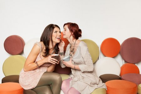 girls whispering a secret and laughing