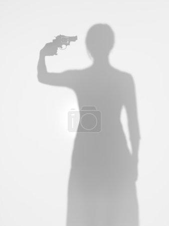 Woman aiming a gun towards her head, silhouette