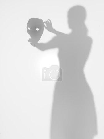 Photo pour Vue de face de la femme tenant un horrormask dans ses mains derrière une surface diffuse - image libre de droit