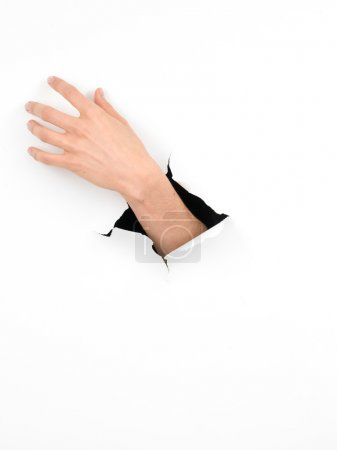 Woman hand reaching out, paper with hole
