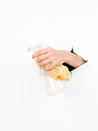 Photo pour Gros plan de la main d'une femme tenant un contenant de détergent liquide et un chiffon à travers un papier blanc déchiré, isolé - image libre de droit