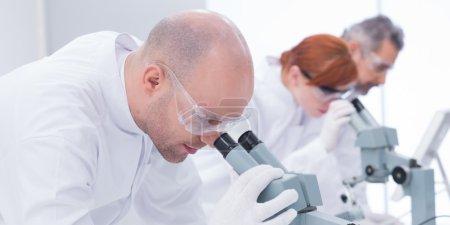 man analyzing under microscope