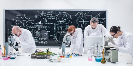 Photo for Close-up of researchers in chemistry lab analyzing under microscope on a worktable around lab tools and colorful liquids and a blackboard with formulas on the background - Royalty Free Image