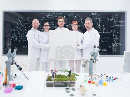 Photo pour Gros plan de cinq scientifiques souriants dans un laboratoire de chimie, tenant en main une bannière vide et confiant à la recherche dans la caméra avec un tableau noir sur le fond - image libre de droit