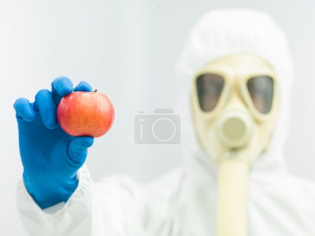 person in protective suit holding ripe apple
