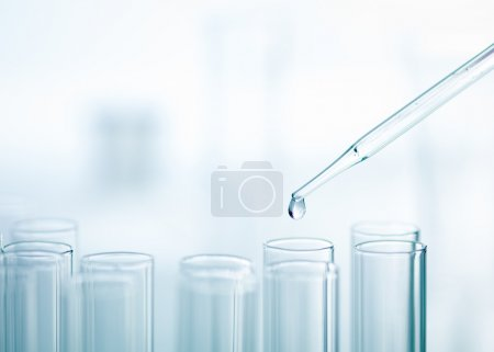 Photo for A close-up of a laboratory glass pipette with emerging drop of substance over one of several test tubes on a light background - Royalty Free Image