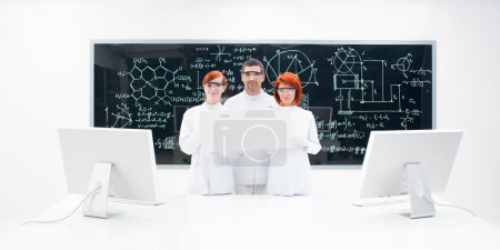 Three lab technicians dressed in white