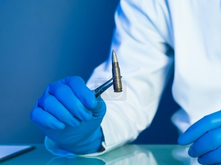 Photo for Person in a white lab coat and blue rubber gloves, holding a bullet with a tweezers on a reflective surface - Royalty Free Image