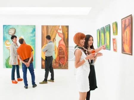 Photo for People in an art gallery talking about the colorful paintings displayed on walls - Royalty Free Image
